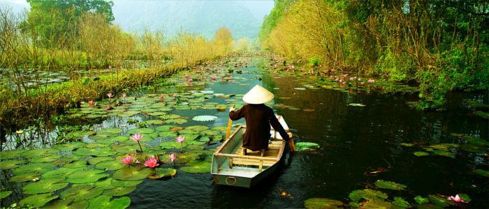 Vietnamese mit dem Boot auf dem Fluss